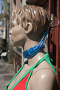 mannequin tight by the neck to a fence with a chain