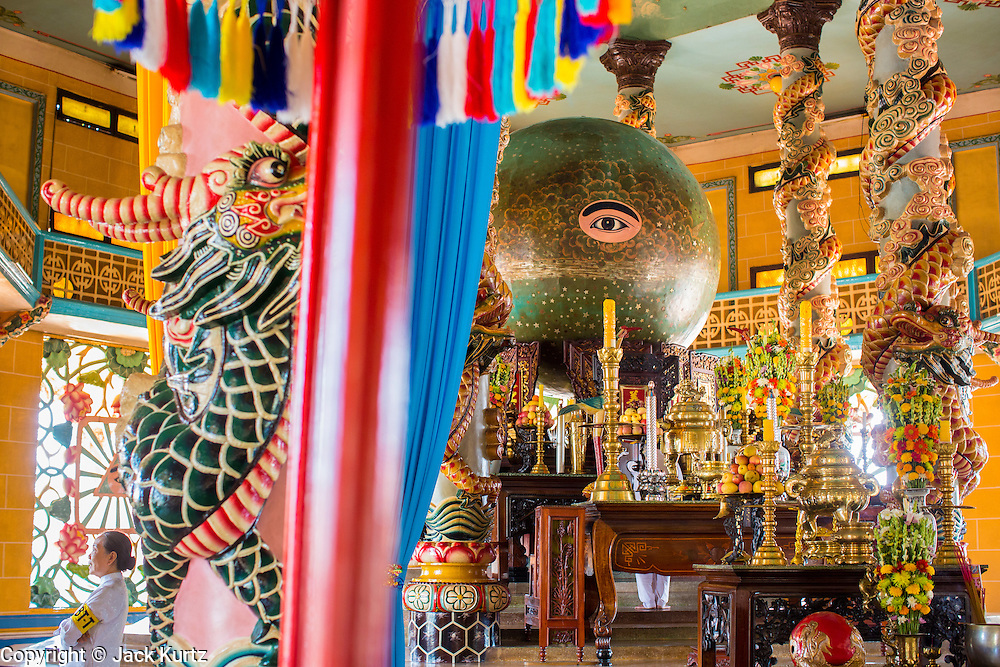 """29 MARCH 2012 - TAY NINH, VIETNAM:  The all seeing eye in the Cao Dai Holy See in Tay Ninh, Vietnam. Cao Dai (also Caodaiism) is a syncretistic, monotheistic religion, officially established in the city of Tây Ninh, southern Vietnam in 1926. Cao means """"high"""" and """"Dai"""" means """"dais"""" (as in a platform or altar raised above the surrounding level to give prominence to the person on it). Estimates of Cao Dai adherents in Vietnam vary, but most sources give two to three million, but there may be up to six million. An additional 30,000 Vietnamese exiles, in the United States, Europe, and Australia are Cao Dai followers. During the Vietnam's wars from 1945-1975, members of Cao Dai were active in political and military struggles, both against French colonial forces and Prime Minister Ngo Dinh Diem of South Vietnam. Their opposition to the communist forces until 1975 was a factor in their repression after the fall of Saigon in 1975, when the incoming communist government proscribed the practice of Cao Dai. In 1997, the Cao Dai was granted legal recognition. Cao Dai's pantheon of saints includes such diverse figures as the Buddha, Confucius, Jesus Christ, Muhammad, Pericles, Julius Caesar, Joan of Arc, Victor Hugo, and the Chinese revolutionary leader Sun Yat-sen. These are honored at Cao Dai temples, along with ancestors.    Photo by Jack Kurtz / ZUMA Press  PHOTO BY JACK KURTZ"""