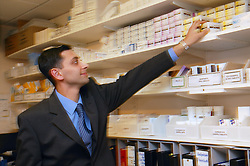 Pharmacist taking nebulised antibiotics from shelf in the Outpatients Pharmacy,