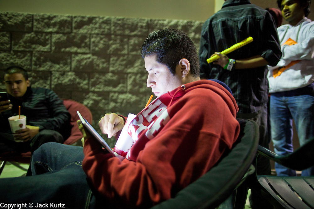 """24 NOVEMBER 2011 - PHOENIX, AZ: 22:54  Liborio Luna (CQ) plays on his iPad and drinks a Jamba Juice while he waits for the store to open at the Best Buy store on Thunderbird and I 17 in Phoenix. He said he wasn't looking for anything in particular and was out to """"play with my iPad and have a Jamba Juice."""" """"Black Friday,"""" the unofficial start of the holiday shopping season started even earlier than normal. Many stores, including Target and Best Buy, opened at midnight. The Best Buy at Thunderbird and I 17 showed a Harry Potter movie on the side of a rented truck in the parking lot to keep people amused while they waited for the store to open.   Photo by Jack Kurtz"""