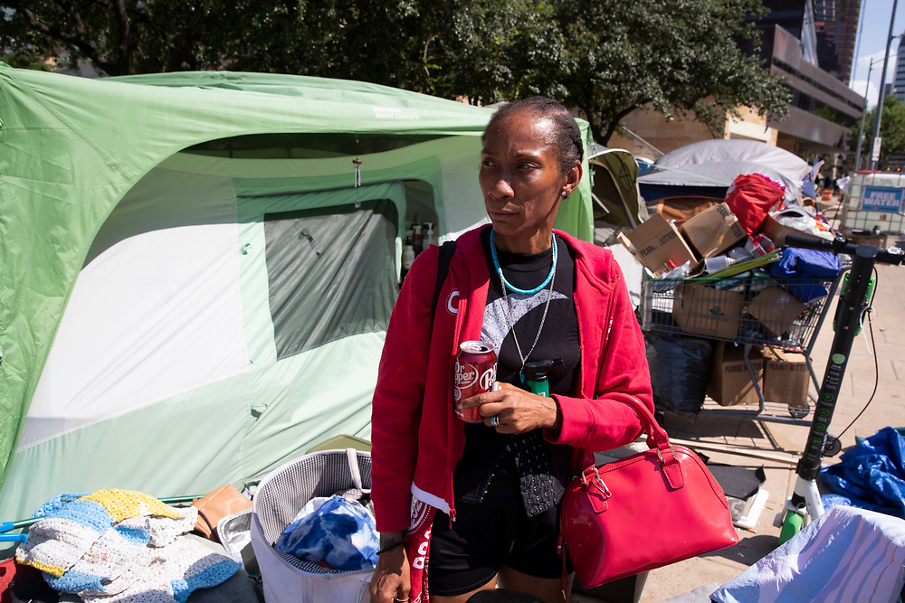 Naquila Chambers-Moore waits as City of Austin  (TX) police supervise while city workers clean out a large homeless protest camp on the north side of City Hall mid-morning. Police arrested multiple homeless who refused to cooperate after several weeks of warnings and offers of assistance.