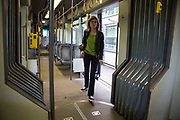 A female Belgian woman enters an empty De Lijn tram in Ghent, Belgium.