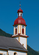 Neustift im Stubaital, the parish church of St. George in the town centre with a blue sky background, Tyrol, Austria