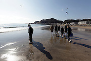group of school children walking on the beach Japan Kamakura