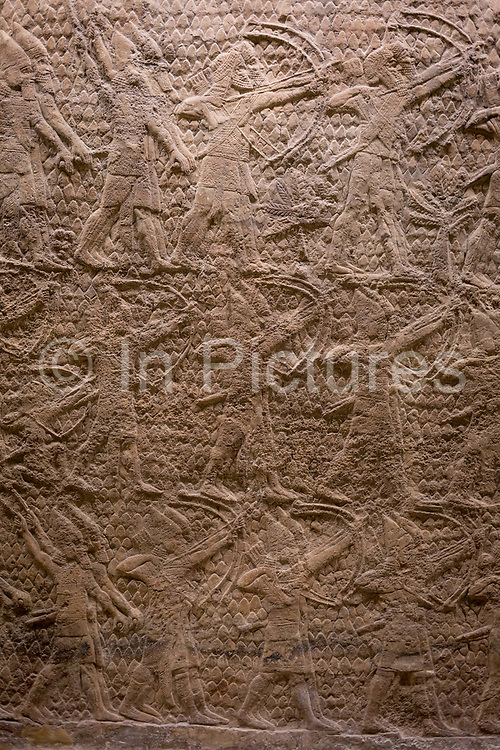 A detail of one ancient Assyrian stone panel carving 700-692BC showing archers attacking the town of Lachish near Jerusalem, in the British Museum, on 11th April 2018, in London, England. The relief was created for the walls of the great palace of the Assyrian king, Sennacherib, in Nineveh. Such scenes demonstrated the consequences of rebelling against the Assyrian empire. Sennacherib is shown as an invincible king presiding over a perfect victory.