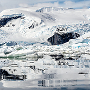 Mountains, ice, snow, and water in a scenic landscape on the Antarctic Peninsula.