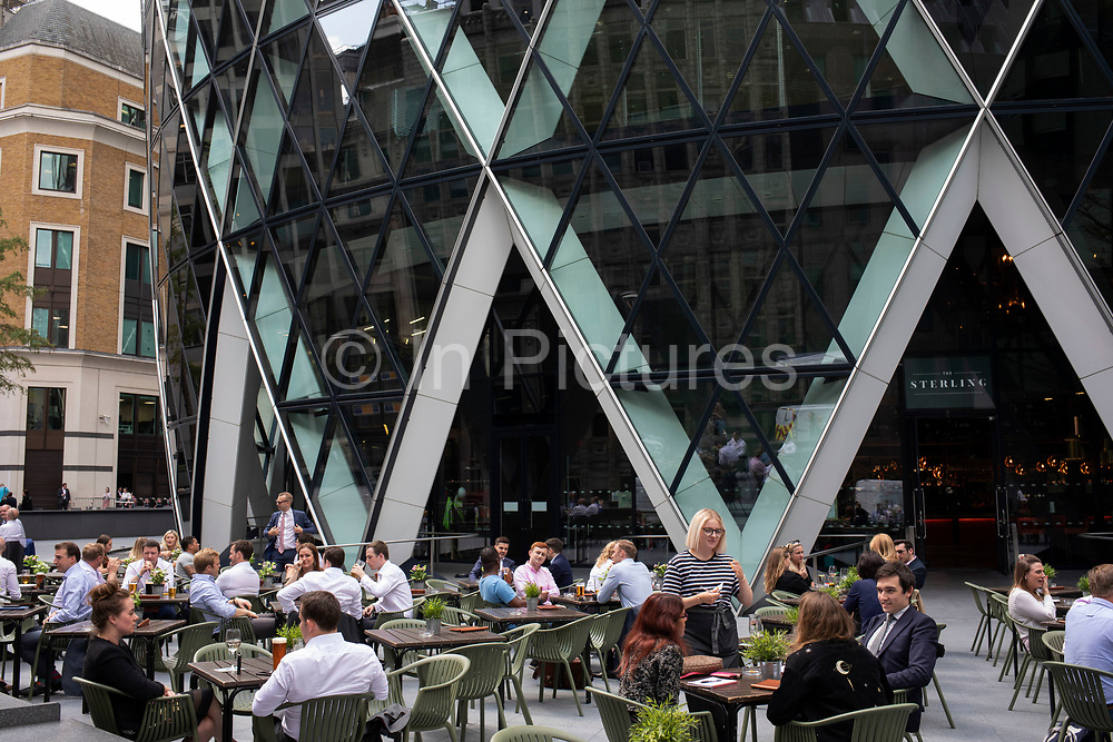 Lunchtime city workers eating at an outdoor terrace restaurant in summertime beneath 1 St Mary Axe, the building also known as The Gherkin in the City of London, England, United Kingdom. This iconic building is one of the best loved buildings in London with its distinctive bullet like shape and twisted glass structure.