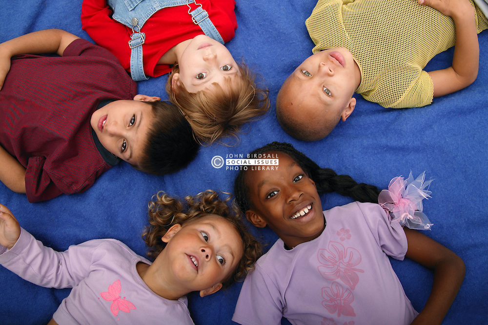 Multiracial group of kids young lying down on ground and looking upwards,