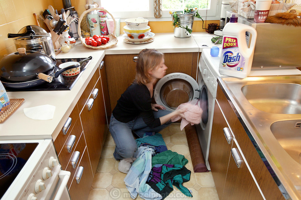 (MODEL RELEASED IMAGE). Kitchens do more than provide a room for cooking, eating, and food storage. Delphine Le Moine, 20, performs laundry duty using the modern laundry machine in her family's kitchen. (From a photographic gallery of kitchen images, in Hungry Planet: What the World Eats, p. 54)