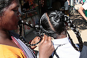 A woman braids the hair of a young girl.  The slum of Cheetah Camp on the outskirts of Mumbai, India is a predominantly muslim community on living on the fringe while the city continues to grow.