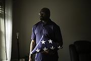 BIRMINGHAM, AL – JUNE 9, 2020: John Hill holds the burial flag honoring his veteran father, Clarence John Hill, Sr., who served honorably in World War II and the Korean War. Hill discovered his father had tested positive for coronavirus only after his death, through a funeral home in Alexander City. CREDIT: Bob Miller for The Wall Street Journal<br /> VETVIRUS