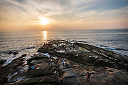 People fish and explore the rocky coastline at sunset at the northernmost tip of Borneo, located in the Malaysian state of Sabah. (August 12, 2019)