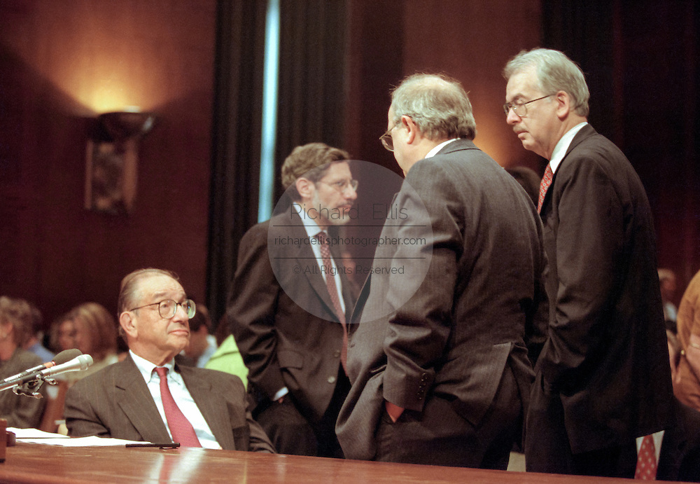 Federal Reserve Chairman Alan Greenspan talks to Senators before testifying in the Senate Banking Committee July 21, 1998 in Washington, DC. Greenspan, in mid-year testimony said the central bank worries more about inflationary pressures than the slowdown in the economy. He promised to 'resist vigorously' any signs of inflationary buildup.