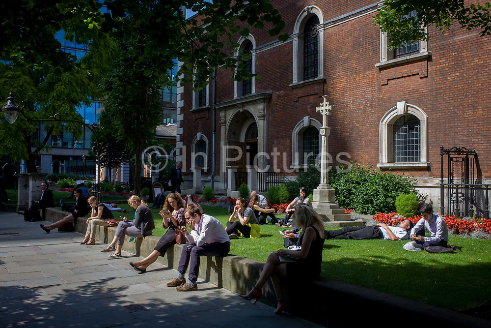 Lunchtime sun for City of London office workers in the grounds of St. Botolph's without Bishopsgate church. <br /> Christian worship has probably been offered at this location at the church of St. Botolph's without Bishopsgate since Roman times. The original Saxon church, the foundations of which were discovered when the present church was erected, is first mentioned as 'Sancti Botolfi Extra Bishopesgate' in 1212. St. Botolph without Bishopsgate may have survived the Great Fire of London unscathed, and only lost one window in the Second World War, but on 24 April 1993 was one of the many buildings to be damaged by an IRA bomb.