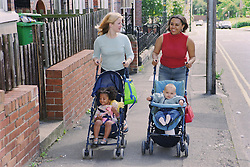 Young mothers pushing children in pushchairs along pavement smiling,