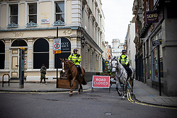 © Licensed to London News Pictures. 26/11/2020. London, UK. Mounted police officers patrol a street in Covent Garden that is closed to the public to create more space for social distancing. The government has announced that London will be in Tier 2 when tiered restrictions are reintroduced once the England-wide lockdown ends on 2 December. Photo credit: Rob Pinney/LNP