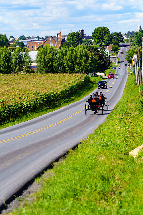 Intercourse, PA, USA - August 30, 2020: Two horse drawn Amish buggies travel on a rural road in Lancaster County.