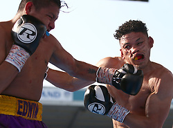 Lyon Woodstock (right) takes a punch from Edwin Tellez during their International Super-Featherweight bout at Elland Road, Leeds.