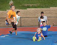 Children, including airborne Olivia Wallace at left,  jump in the high jump pit at the Middletown High School track during the Twilight Track and Field Series on Tuesday, July 30, 2013.