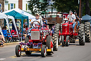 Members of the Central Pennsylvania International Harvester Collectors Chapter 17 drive tractors in the Independence Day parade in Millville, Pennsylvania on July 5, 2021.