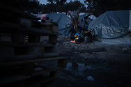 Two men cooking dinner on a wood fire. About 20000 are living in a makeshift camp nearby the city of Moria on the island of Lesbos in miserable conditions, most of the without water, electricity nor sanitary facilities.  Federico Scoppa