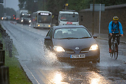 © Licensed to London News Pictures. 01/10/2021. London, UK. A car drives through a large puddle during heavy rain near Greenwich Park in South East London. Rain showers are forecasted to continue in parts of London and South East England for the rest of the week.  Photo credit: George Cracknell Wright/LNP