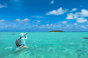 Big Cook Island bonefish makes a run for coral lined drop off in the bay with angler sprinting to give herself a chance.