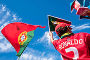 Portuguese supporter dressed with Crsitiano Ronaldo's shirt, celebrating with national flags while   awaiting for the football team to arrive at Alameda Dom Afonso Henriques, in Lisbon. Portugal's national squad won the Euro Cup the day before, beating in the final France, the organizing country of the European Football Championship, in a match that ended 1-0 after extra-time.
