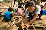 25 MAY 2013 - MAE SOT, TAK, THAILAND: A Burmese woman makes thatch panels to repair her home in an unofficial village of Burmese refugees north of Mae Sot, Thailand. They live on a narrow strip of land about 200 meters deep and 400 meters long that juts into Thailand. The land is technically Burma but it is on the Thai side of the Moei River, which marks most of the border in this part of Thailand. The refugees, a mix of Buddhists and Christians, settled on the land years ago to avoid strife in Myanmar (Burma). For all practical purposes they live in Thailand. They shop in Thai markets and see their produce to Thai buyers. About 200 people live in thatched huts spread throughout the community. They're close enough to Mae Sot that some can work in town and Burmese merchants from Mae Sot come out to their village to do business with them.   PHOTO BY JACK KURTZ