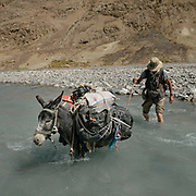 """Paul Salopek during a river crossing. Trekking from Baiqara camp into the Tash Köpruk valley, leading to Pakistan. Guiding and photographing Paul Salopek while trekking with 2 donkeys across the """"Roof of the World"""", through the Afghan Pamir and Hindukush mountains, into Pakistan and the Karakoram mountains of the Greater Western Himalaya."""
