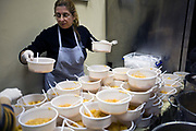 Volunteers prepare and serve potato soup for the poor and homeless in a Municipal Soup kitchen in Athens, Greece