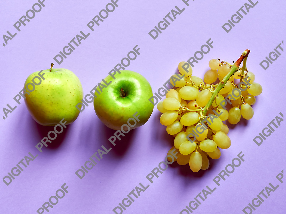 Above view of isolated set of a green apple with a bunch of sweet seedless grapes in studio with pastel violet background