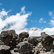The summit of Mt Kilimanjaro is in the distance, partly obscured by clouds, as seen from the trail between Moir Hut Camp and Lava Tower at approximately 14,500 feet. In the distance is the summit, partly hidden by clouds.