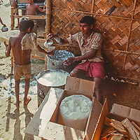Homeless women and schildren scramble for a ration of milk and biscuits at a refugee camp near Dhaka, Bangladesh, in 1977.  They are victims of a 1970 cylcone and subsequent war of indpendence that left many of them destitute, widowed and violated.