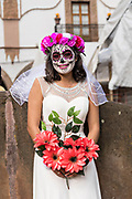 A young woman dressed in La Calavera Catrina bride costume during the Day of the Dead or Día de Muertos festival October 31, 2017 in Patzcuaro, Michoacan, Mexico. The festival has been celebrated since the Aztec empire celebrates ancestors and deceased loved ones.