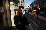 Evening light illuminating a couple walking while holding on to one another along Piccadilly in London, England, United Kingdom.