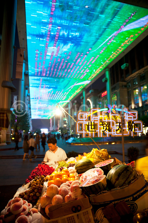 Fruit seller at The Place is a new shopping street located in Beijing CBD. The huge overhead LCD screen designed by Jeremy Railton from Hollywood, is 250m long 30m wide. The Beijing Central Business District, or CBD is the primary area of finance, media, and business services in Beijing, China. It occupies 4km2 of the Chaoyang District on the east side of the city. As the city is becoming one of the most important international financial centers in China so the CBD grows in height as skyscrapers rise into the sky.