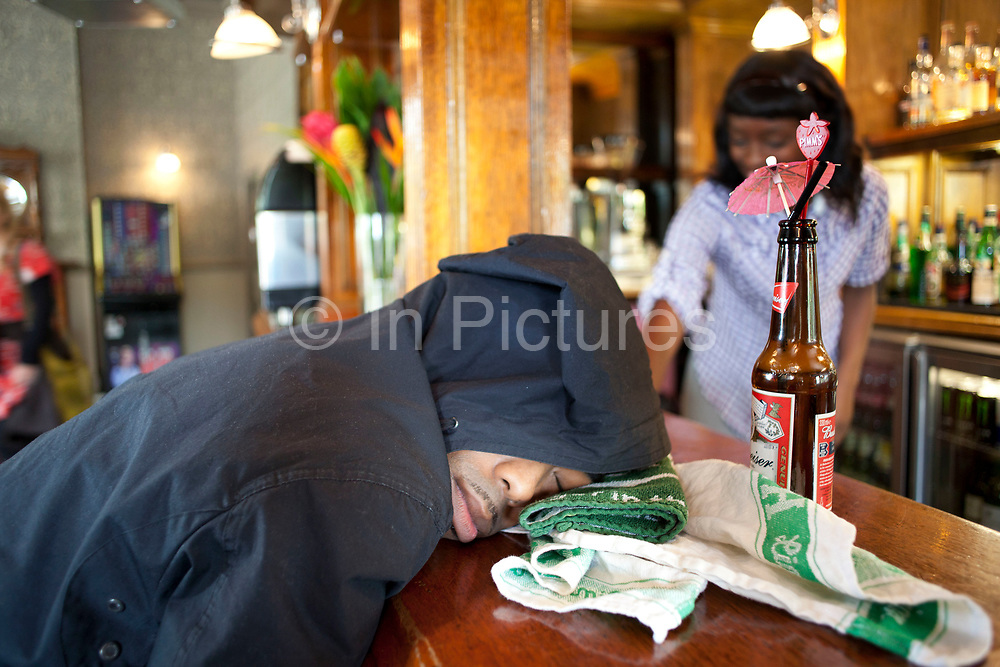 Man asleep at the bar in the Birdcage pub on Columbia Road in East London, England, UK. Resting his head on a beer towel, and with a bottle of Budweiser with a cocktail umbrella in the top, this member of the public was genuinely fast sleep.