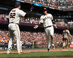 Oct 3, 2021; San Francisco, California, USA; San Francisco Giants starting pitcher Logan Webb (62) greets teammate Wilmer Flores as they both score on a single by Buster Posey against the San Diego Padres during the third inning at Oracle Park. Mandatory Credit: D. Ross Cameron-USA TODAY Sports