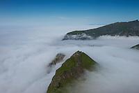 Mountain peaks emerge above fog at Unstad, Vestågøy, Lofoten Islands, Norway