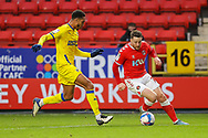 AFC Wimbledon defender Terell Thomas (6) and Charlton Athletic forward Conor Washington (14) during the EFL Sky Bet League 1 match between Charlton Athletic and AFC Wimbledon at The Valley, London, England on 12 December 2020.