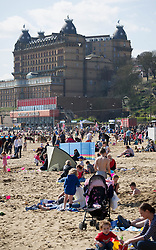 (c) Licenced to London News Pictures 07/04/2015. Scarborough, North Yorkshire, UK. People enjoy the hot weather in the sun on Scarborough South Bay beach. Photo credit : Harry Atkinson/LNP