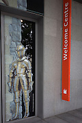 Suit of medieval armour and sign for the Tower of London's Welcome Centre.