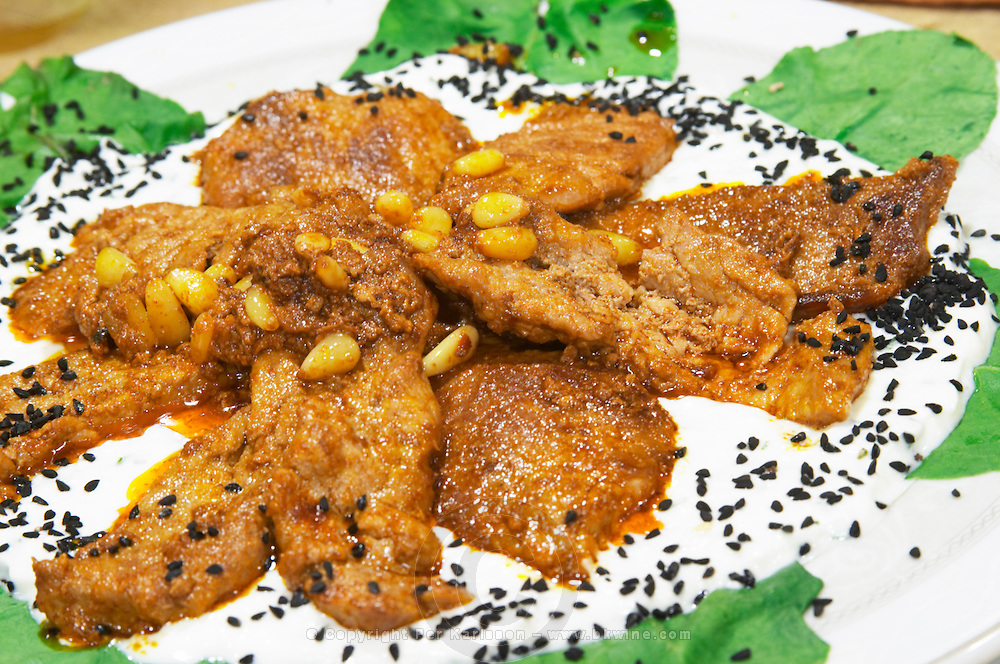 Fried tuna fish in yoghurt sauce with pine nuts. Efendi Efendy traditional Turkish and Ottoman Restaurant, The Block, Tirana. Albania, Balkan, Europe.