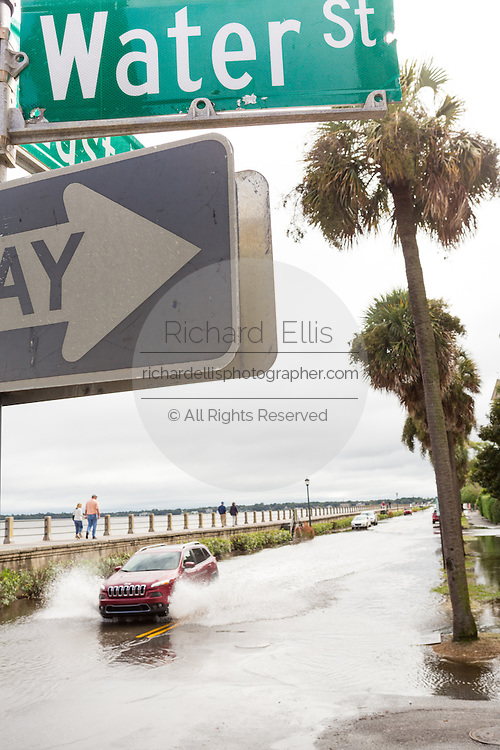 A car plows through floodwater along the Battery past Water Street in the historic district after record breaking storms dumped more than two feet of rain on the lowcountry October 5, 2015 in Charleston, South Carolina.