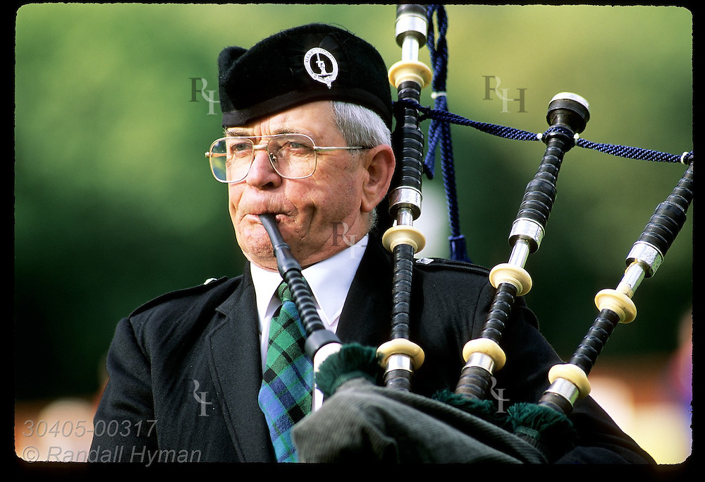 Man plays bagpipes as he parades during Highland Games called the Loch Ness Gathering at Fort Augustus, Scotland.