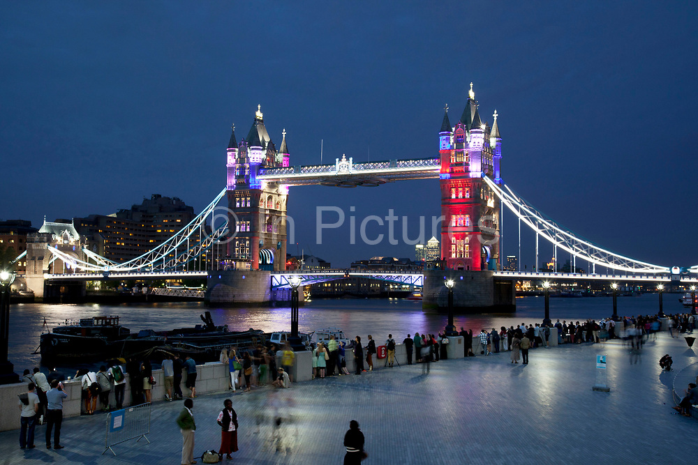 Tower Bridge light show to mark the countdown to the London 2012 Games. A new look to the central London landmark on the River Thames with the public gathering on the river path in the evening light to watch as the bridge was lit up.