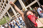 """29 JULY 2010 - PHOENIX, AZ: Jenny Sanchez (CQ) leads a chant against Sheriff Joe Arpaio on Washington St in Phoenix Thursday. Dozens of people were arrested during protests against SB 1070 across central Phoenix Thursday. US Judge Susan Bolton's ruling Wednesday stopped four of SB 1070's more than a dozen provisions from going into effect. She wrote, """"The court also finds that the United States is likely to suffer irreparable harm if the court does not preliminarily enjoin enforcement of these sections,"""" she states in the ruling. """"The balance of equities tips in the United States' favor considering the public interest.""""     PHOTO BY JACK KURTZ"""
