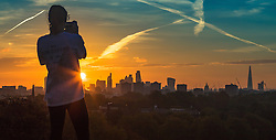 Primrose Hill, London, October 28th 2016. A woman photographs the city skyline as dawn breaks over London.