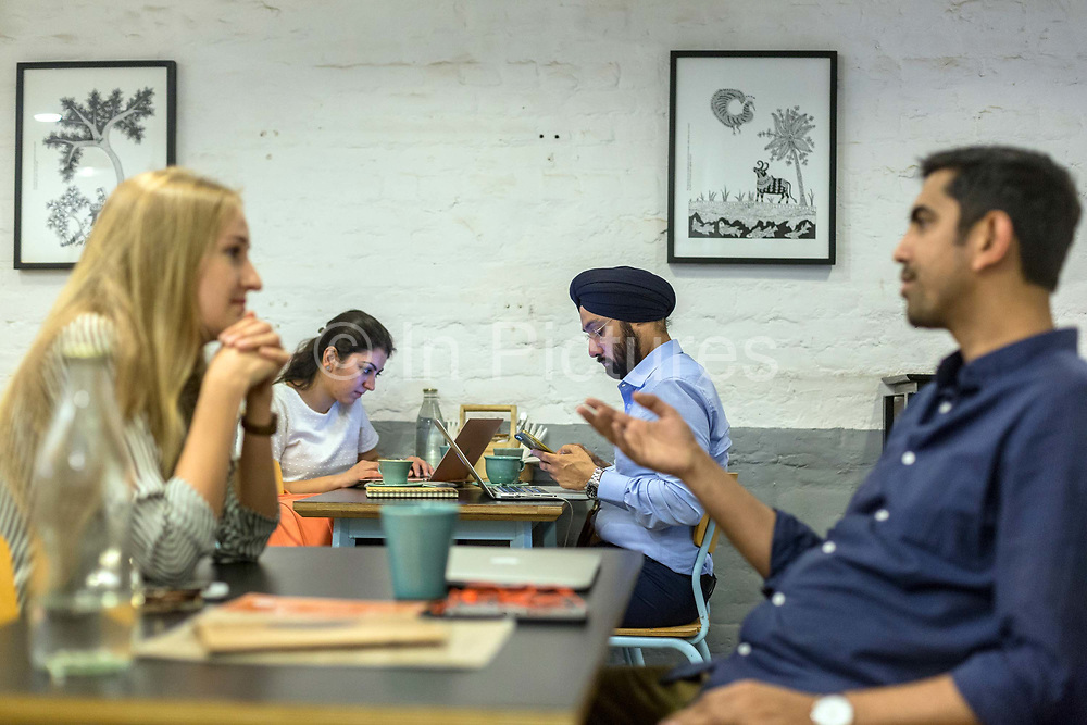 A couple chat at Blue Tokai coffee shop in Champa Gali, New Delhi, India. Champa Gali is the latest and most intimate of Delhis urban creative villages.